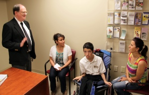David White greets a CRS family as they visit with a CRS social worker during the seizure clinic
