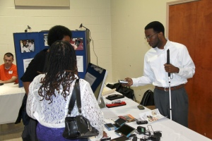 Attendees view different assistive technology devices at the AIDB booth at the 2013 symposium