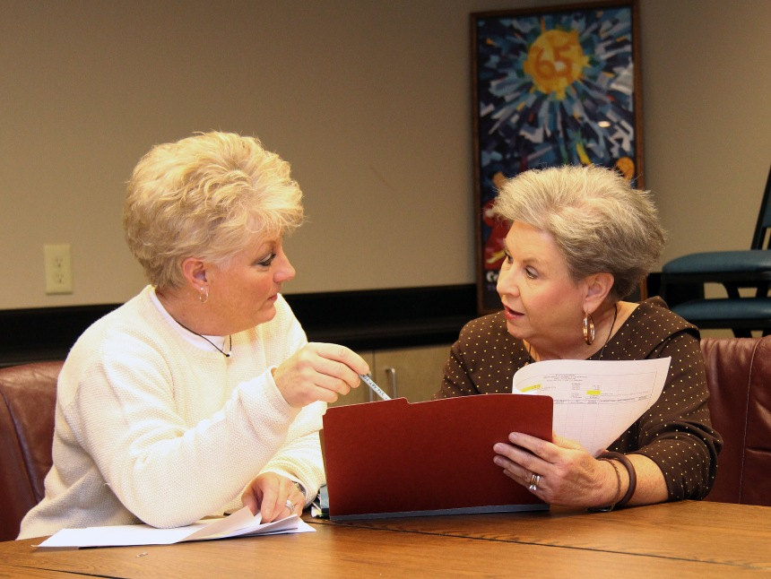 New EI Assistant Coordinator Amy Blakeney looks over over budget sheets with Betsy Prince, statewide EI coordinator