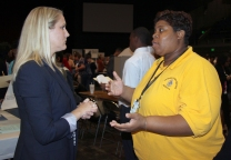 A staffer from Wenonah High School speaks with an exhibitor