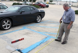 Papp measures the length and incline of a wheelchair ramp outside the Career Center in Cullman