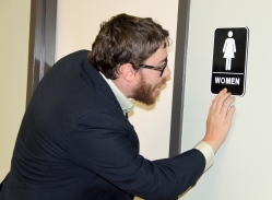 Blind Services Accessibility Specialist Jason Martin tests the Braille on a bathroom sign
