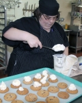 A GATE Program trainee frosts cookies in the bakery