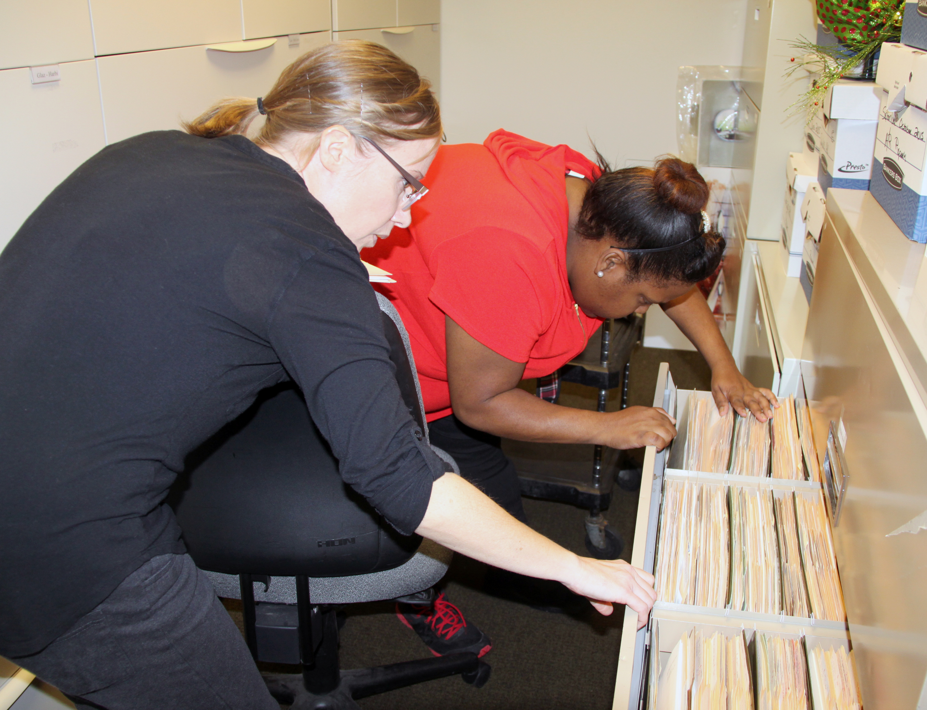 Wendy Lawless, a job coach with UCP of Greater Birmingham, works with a GATE Program trainee in the file room of The Club