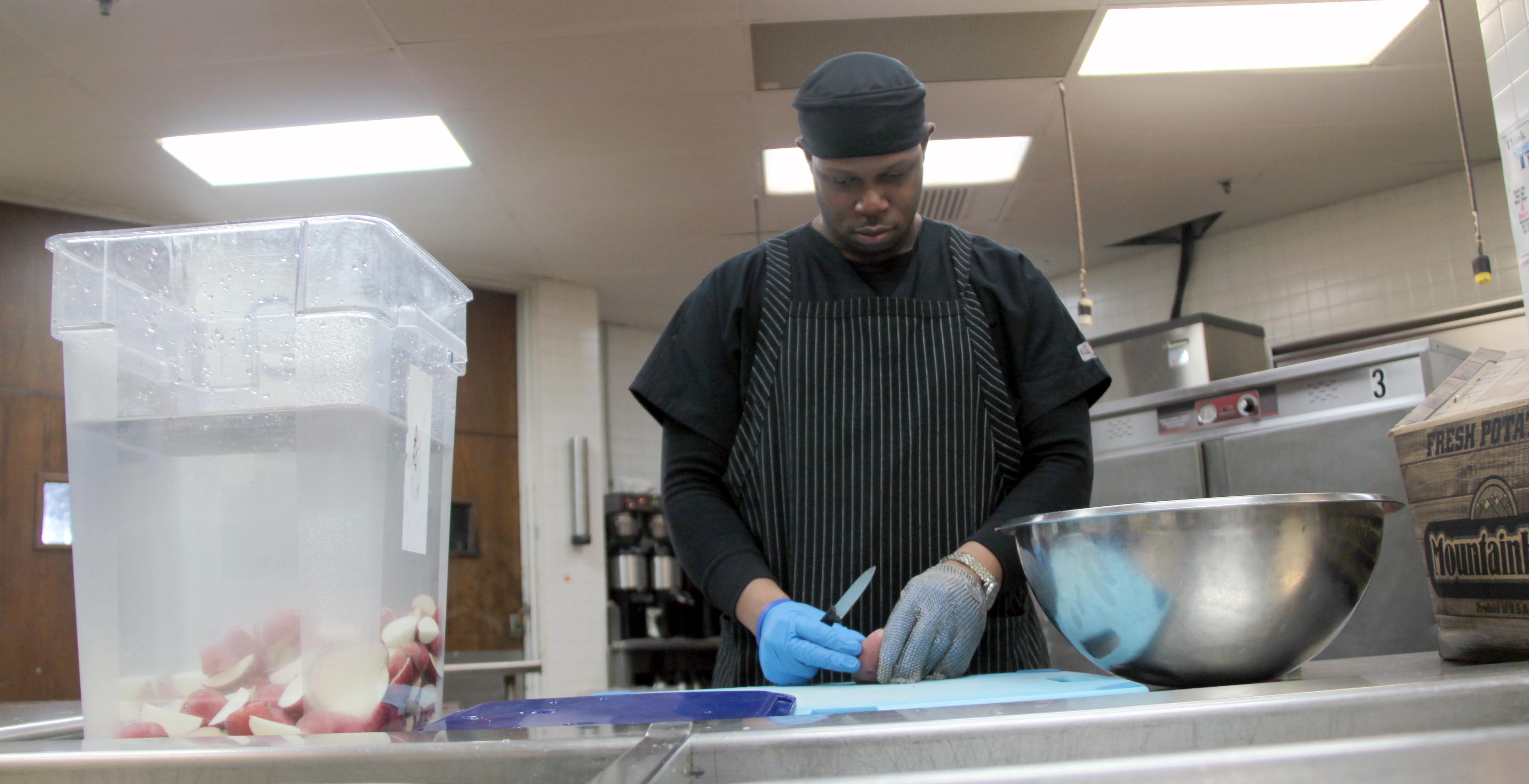 A trainee preps potatoes