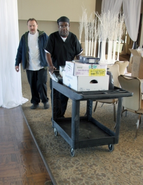 A trainee pushes a cart of supplies to the kitchen