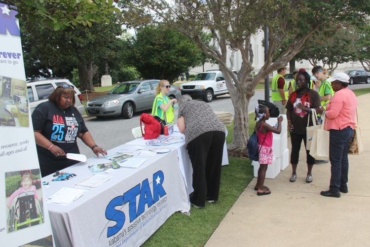 In this file photo, STAR Director Helen Baker sets up a table for last year's ADA bus tour stop at the Capitol