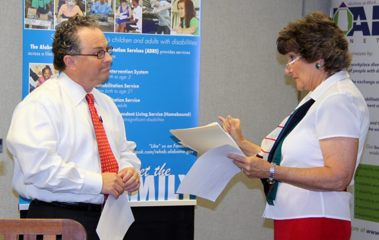 Business Relations Administrator Peggy Anderson interviews ABLN Vice Chairman Charles Wilkinson before a July 14 board meeting