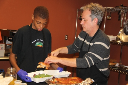 Beautiful Rainbow Project Founder Chip Rowan assists a student in preparing a to-go lasagna
