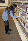 Amanda Sigler, an employee at the Gadsden Public Library, places a book on the shelf