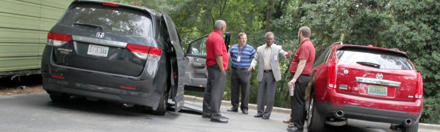 Board members Eddie Williams and Jimmie Varnado speak with members of the Adaptive Driving Program team following the board meeting
