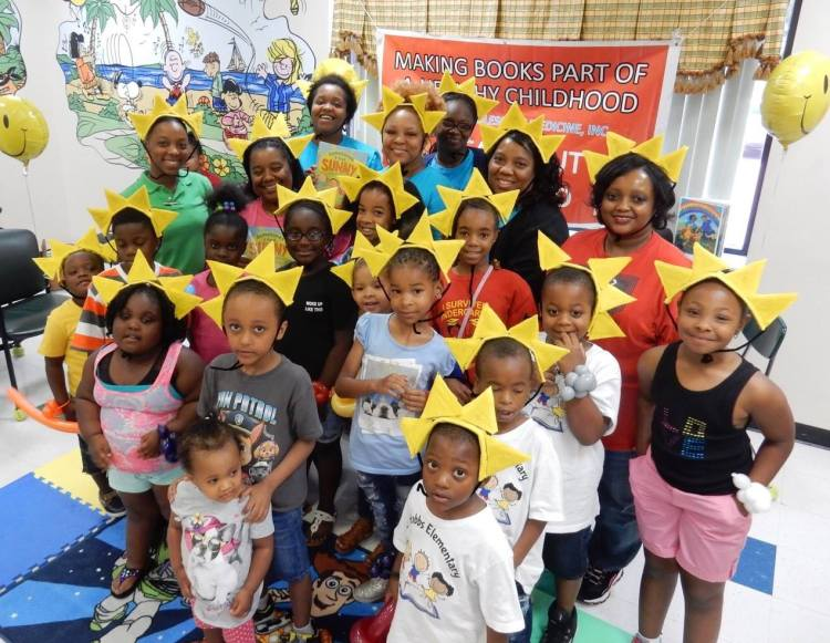 Children wear sunburst hats for a group photo at the Rx for Summer Reading kickoff event in Selma