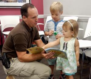 A volunteer reads aloud to children at an event held at West Alabama Pediatrics