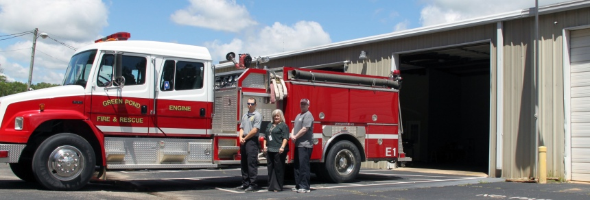 Dustin Rowe, Tammy Lovell, and Joseph Hall stand in front of a fire truck