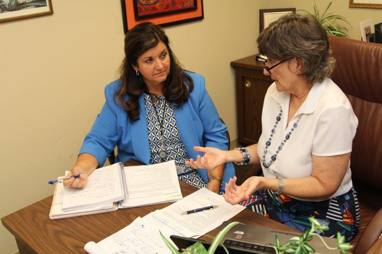 Incoming Business Relations Administrator Leslie Dawson trains with Peggy Anderson, outgoing business relations administrator