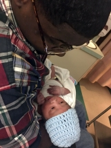 Ronald Witherspoon holds his newborn son while in the hospital