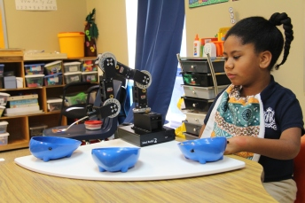 Diyari tells the robotic arm which of the three bowls she wants to eat from
