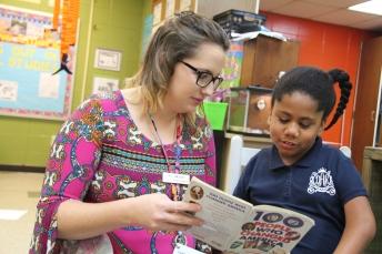 Diyari reads a book with her teacher, Cassie Jacobs