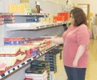 Soliday stocks shelves while working at the Gentry campus store.